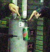 路上の私製灰皿を指弾する参加者の指と傘