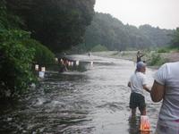 川の中に立って、灯籠を流れに乗せるスタッフ