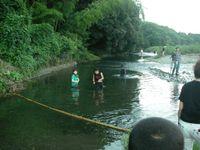 灯籠の流れを調整する竹竿とスタッフ