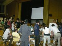 コップを手に集まる聴衆