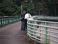橋の上の見学者に取材する地元紙記者(後ろ姿)