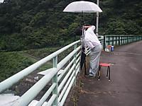 橋の上で傘をさし、下流側の撮影をする職員。