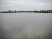 灰色の水をたたえた湖。対岸には住宅が見える。