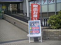 ビルの2階と駅を結ぶ通路に出された「献血のお願い」幟。その前には魚民の「飲み放題」という看板が。