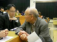 階段教室で後方の席の卒業生二人と懇談される前教授