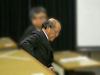 講演者席でハンカチで口元を拭い緊張の様子の教授