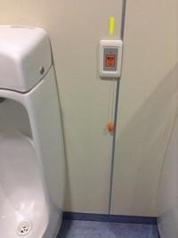 小便器の脇、高さ1.2m程のところにある非常呼び出しボタンと、そこから下がるヒモ。下端にはオレンジ色のつまみが付いている。