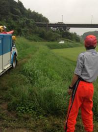 松川記念塔へ続く農道の向こうで乗ってきた乗用車が傾いている。JAFのレッカー車は農道に入れない。