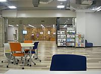 小さいテーブルとキャスター付きの色鮮やかな折りたたみ椅子が配置された図書館入口脇のロビー