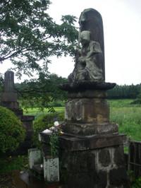 真新しい白い菊が供えられた高さ3メートルほどの台座に載った石像