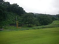 田圃の向こうに慰霊碑と線路が見える