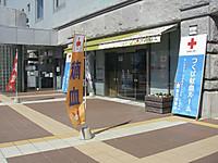 建物の前に「献血」と書いた幟が3本、入り口の両脇に「つくば献血ルーム 献血実施中」という高さ2メートル、幅70センチメートルほどの立て看板