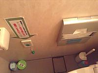 扉を開けて入ると右手に便器、正面の壁の右手には使い捨て便座シート、中央やや左下に紐も下がっている非常呼び出しボタン、その左にトイレットペーパーホルダー。