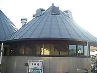 大きな高窓一周する円形の建物に円錐形の屋根