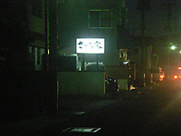 闇夜に浮かび上がる「さかな家」の看板