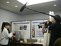 アンコウ汁を作る寸胴鍋の前に女性レポーターが立ち、向かって右側にカメラ・音声・照明