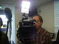 正面にTVカメラを担いだ男性、その背後からLEDライトで照らされ、向かって左には音声収録用の大きなマイク