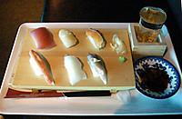 寿司台に並べた六貫の握り寿司と升に入ったコップ酒を収めたトレイ