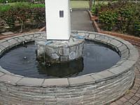 直径3メートルほどの池の中央にある島から水が流れ出ているが、どう見ても石造りに似合わないビニールホース