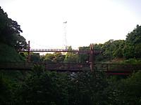 谷の奥の道から眺めると大小2つの吊り橋の向こうに東京電力の鉄塔