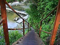 滝壺脇へ降りる狭い鉄の階段。傾斜は急で20段以上。降りた先に川を渡る飛び石が見える。