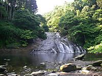 正面から見た粟又の滝。緩やかな岩肌を水が流れ落ちてきている。