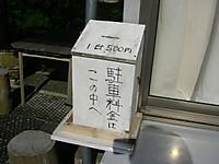 町営駐車場出入口脇の小屋に紐でくくりつけられた「駐車料金はこの中へ」「1台500円」と手書きされた白い木箱。