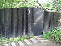 高さ2メートルほどの塀に「婦人用」を示すピクトグラムとドアの付いたトイレ。
