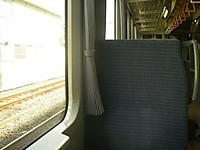 八高線の車内。ボックスシートとカーテン。後方上部に吊り革。