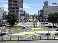 窓からの眺め。青空の下、駅前から片側3車線の道路がのびている。