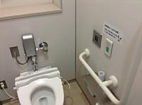 トイレ個室に入ると左側に便器。座ると左側に来る奥の壁にはL字手すりや非常呼び出しボタン。水を流すときは非常ボタンの隣のセンサーに手をかざす。