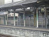 フェンスの手前は閉鎖された旧1番線。その向こうに下仁田行きの白い電車が止まっており、天井には「上信線のりば→0」のライトボックス看板が
