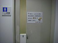 共用の男性用トイレの扉に貼られた注意書き。「採血直後は、脳貧血防止のため、座位でお願いします。」「座位」の字が強調され、便座のイラストも。