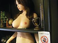 全裸のラブドールが立って収まっている本棚。脇には「手を触れないでください」という注意書きが貼ってある。