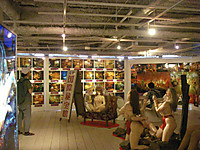 入口付近から会場内を見たところで、壁にはラブホテルの室内写真が4段で壁2面に、中央には「元祖国際秘宝館」の看板(高さ約2メートル)、他に秘宝館にあった裸体女性のマネキンが多数配置。