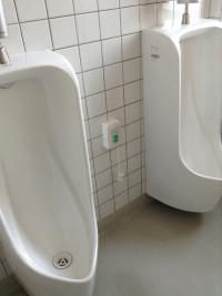 並んだ小便器の間の壁に取り付けられた非常呼び出しボタンは膝ほどの高さに。