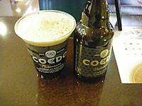 テーブルに並ぶプラスチックコップに注がれた黒ビールとずんぐりとしたビール瓶