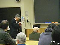 大教室の演壇脇でピンマイクの調整をする男性(Y教授)。最前列には小柄な男性(S元教授)が。