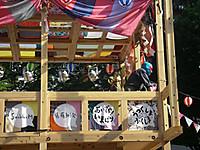 広場の中央に組まれた櫓の上から見下ろすレスラーマスクの怪人(竜田一人さん)