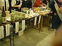 販売用にテーブルに並べられた料理や飲物。後ろには売り子の女性。