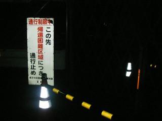 道を塞ぐバリケードと手間にある「この先 帰還困難区域につき 通行止め」の看板。