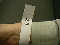 手首に巻かれた紙テープには23という番号が手書き
