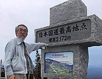 「日本国道最高地点」の石碑に手をついて振り返る筆者