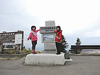 石碑の前の石に乗る襷をかけた2人の女性。