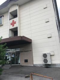 玄関上の白壁に赤十字マークのある2階建て洋館。壁には「諏訪赤十字血液センター」と。
