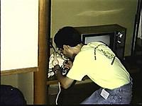 客室の電話を開け、鰐口クリップでモデムとの接続を試みる後ろ姿