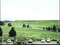 駐車場の先に草原、道路、草の生えた丘