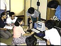 畳敷きの和室で座卓に置かれたパソコンを使いデモンストレーションを行う遺伝研職員の女性