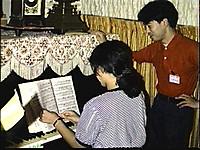ロビーに置かれたピアノを弾く女性とその脇に立つ男性