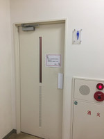 廊下に面した男性用トイレの入口、ドアに注意書き